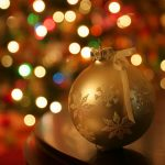 A gold Christmas tree ornament with a blurry Christmas tree in the background.